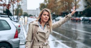 woman-hailing-an-uber-in-rain